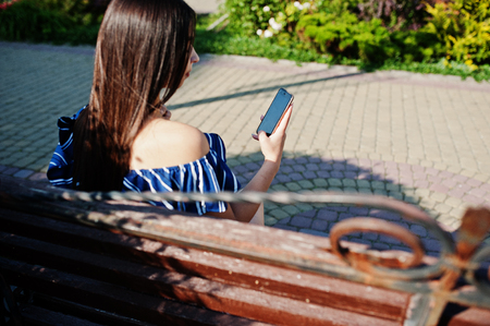 livestream: Gorgeous brunette girl sitting on bench at street of city and looking on phone, wear on blue striped dress. Stock Photo