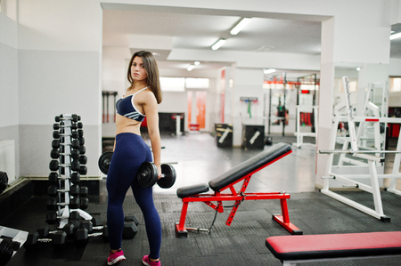 Young beautiful woman doing exercises  and working hard in gym and enjoying her training process. Imagens