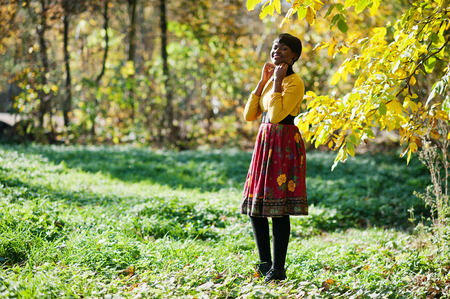 African american girl at yellow and red dress at autumn fall park.