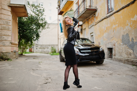 Elegant blonde girl wear on black leather jacket posing at streets of town background luxury car.