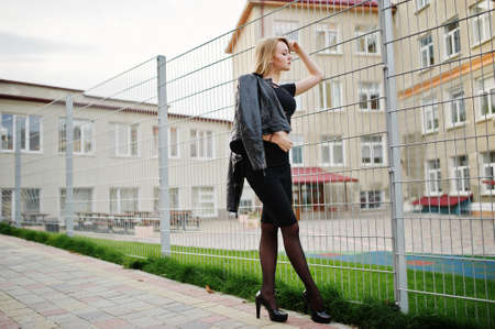Elegant blonde girl wear on black posing at streets of town against iron cage.