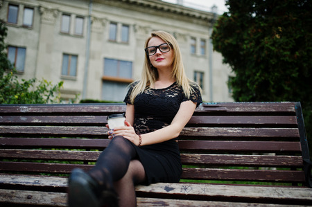 Elegant blonde girl wear on black posing at streets of town, sitting on bench with cup of coffee at hands.