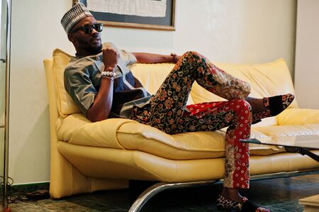 Rich african man sitting on sofa at his appartment. Portrait of successful black man indoor.