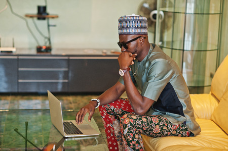 Rich african man sitting on sofa at his appartment and working on notebook.