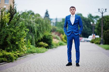 プロムの日に公園で舗装のポーズ正式な派手なスーツでハンサムな若い男の肖像画。