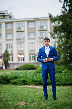 Portrait of a handsome young guy dressed in cool suit posing on the lawn on his prom day.