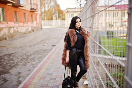 Fashion outdoor photo of gorgeous sensual woman with dark hair in elegant clothes and luxurious sleeveless fur coat against iron fence at autumn city.