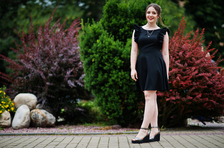 Portrait of a gorgeous young girl in black dress walking on the pavement in the park on a prom day.