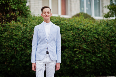 Portrait of a fashionable and stylish high school graduate in elegant tuxedo posing outdoor with bushes on the background.