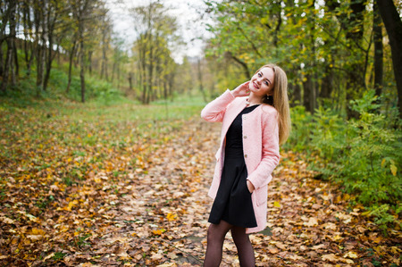 Young blonde girl at pink coat posed on autumn park.