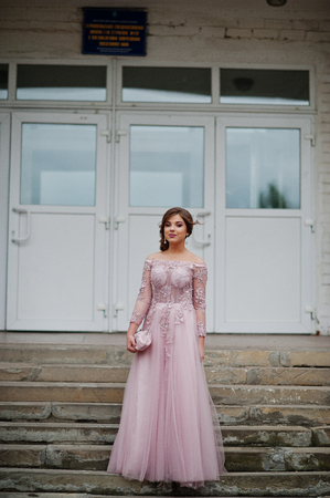 Portrait of an attractive girl standing and posing on the stairs in amazing gowns after high school graduation. Фото со стока