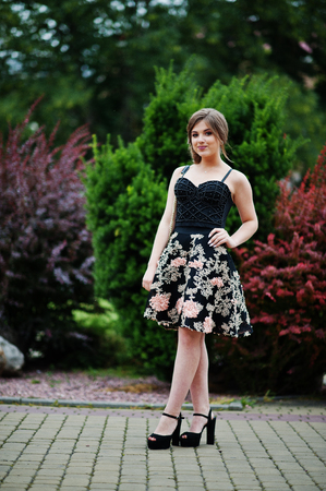 Portrait of a gorgeous young girl in black floral dress walking on the pavement with leather bag in the park on a prom day. Stock Photo