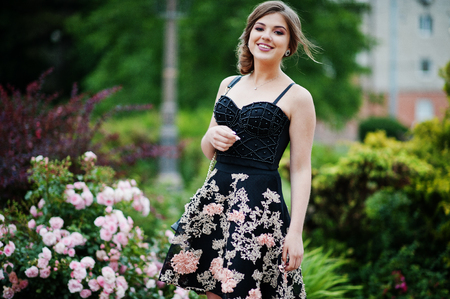 Portrait of a gorgeous young girl in black floral dress walking on the pavement with leather bag in the park on a prom day. Фото со стока