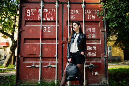 rocker girl: Stylish brunette girl wear on leather jacket and shorts with backpack against shipping container.