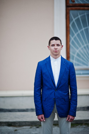 Portrait of a handsome young guy dressed in cool suit posing next to the wall on his prom day.
