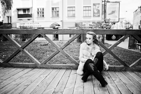 Blonde girl at fur coat sitting on wooden floor outdoor.
