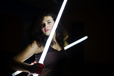 Curly brunette plus size model with two long led lamp at black room.