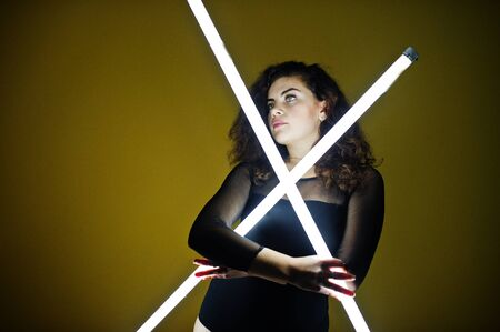 Curly brunette plus size model with two long led lamp against yellow wall.