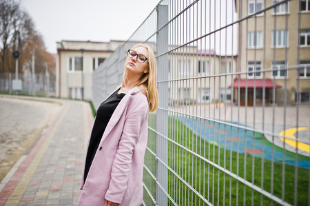Blonde girl at glasses and pink coat, black tunic and handbag posed against fence at street.