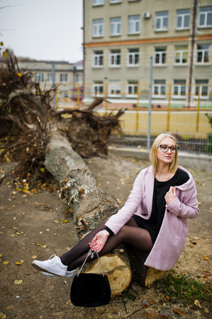 Blonde girl at glasses and pink coat, black tunic sitting on cut tree.