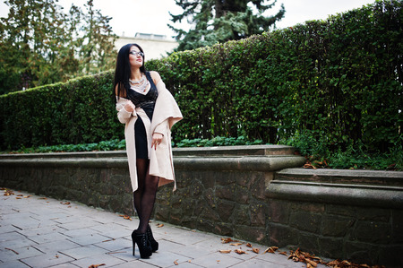 Black hair sexy woman in glasses and coat posed on street.