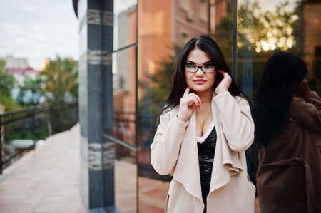 Black hair sexy woman in glasses and coat posed against building with modern windows.