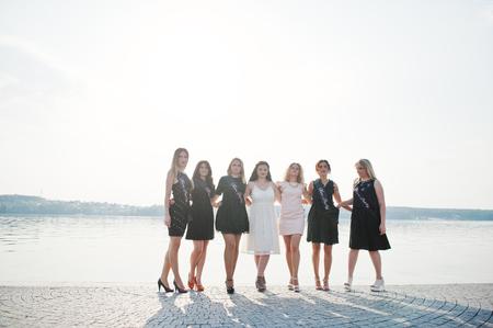 O grupo de 7 meninas veste no preto e 2 noivas no partido de galinha contra a praia ensolarada. Foto de archivo