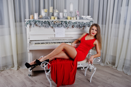 Fashionable gorgeous woman at red long evening dress sitting at studio against piano with candles new year decor.