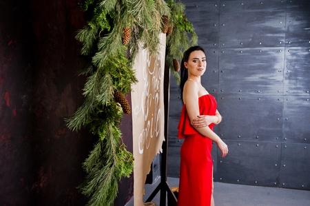 Brunette girl in red dress posed near new year decoration in studio room.