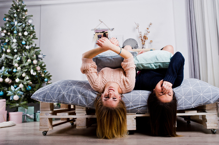Two beautiful girls friends wear in warm sweater and leg warmers (gaiters) play with pillows on bed against new year tree with christmas decoration.  Stock Photo