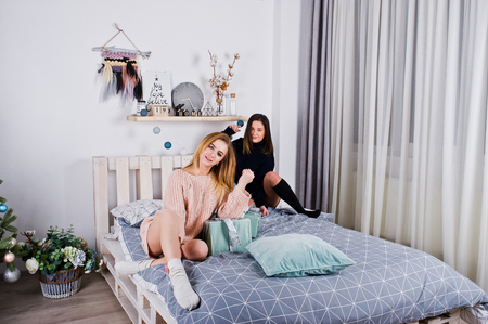 Two fun beautiful girls friends wear in warm sweater and leg warmers (gaiters) with gifts boxes on bed against new year tree with christmas decoration.