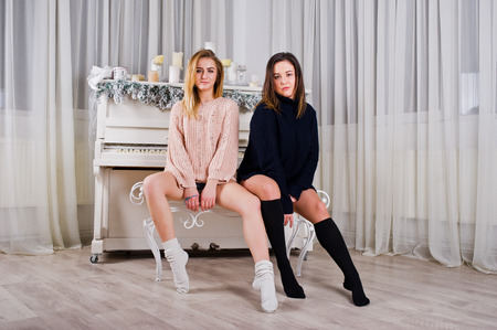 Two  beautiful girls friends wear in warm sweater and leg warmers (gaiters) against new year piano with candles christmas decoration.