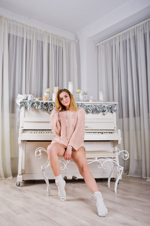 Blonde beautiful girl wear in warm sweater and leg warmers (gaiters) against new year piano with candles christmas decoration.