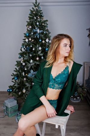 Sexy blonde model in green lingerie against new year tree sitting on chair at white room.