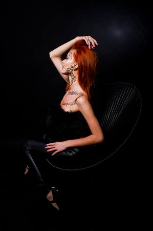 Fashion model red haired girl with originally make up like leopard predator isolated on black. Studio portrait on chair.