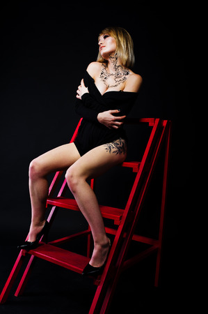 O retrato do estúdio da menina loura com compõe originalmente no pescoço e na tatuagem na coxa, desgaste no vestido preto no fundo escuro, sentando-se na escada vermelha.