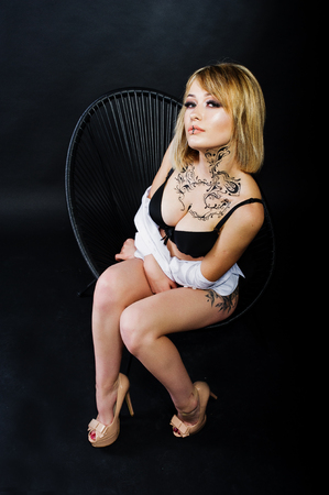 Studio portrait of sexy blonde girl with originally make up on neck and tattoo on thigh, wear on black underwear at dark background, sitting on chair. Stock Photo