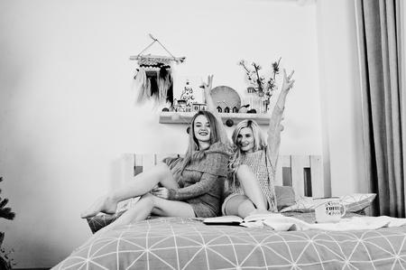 Two elegante blonde girl wear on warm tunic sitting on bed.