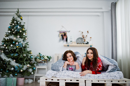 Two girlfriends wear on winter sweaters having fun on bed at room with chrismas decorations.