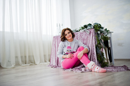 Girl wear on winter sweater sitting against table at room with chrismas decorations.