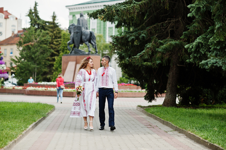 Lovely wedding couple in ukrainian traditional embroidered clothing walk with a bouquet in an old town. Stock Photo