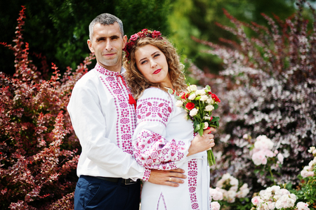 Cute wedding couple in ukrainian traditional clothes posing next to the bushes in the park. Stock Photo