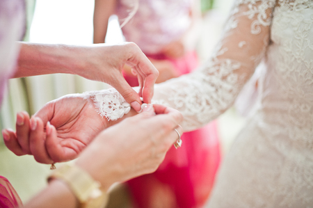 Lovely bridesmaids tying knots on brides cuffs before her wedding ceremony.