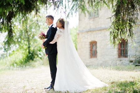 Romantic lovely newly married couple posing in the park by the medieval castle on their wedding day. Stock Photo