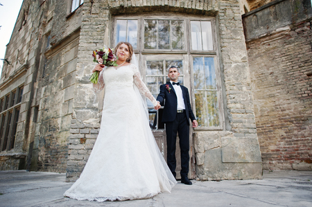 Romantic lovely newly married couple posing by the medieval castle on their wedding day. Stock Photo
