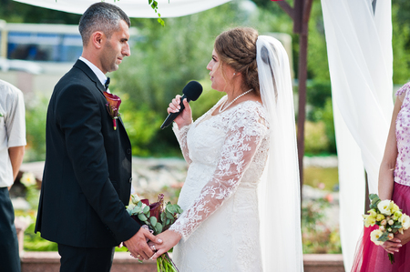 Wedding couple making vows outdoor under the floral arch in front of many guests. Stock Photo