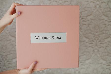 포토 북 또는 사진 앨범 안에 부드러운 핑크 웨딩 상자를 들고 여성 손.