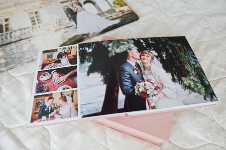 Pages with wedding photos of a photobook or photo album on bed. Stock Photo