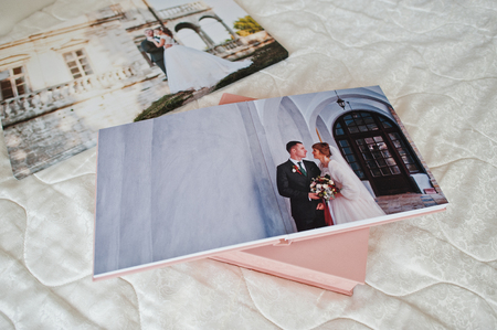 Pages with wedding photos of a photobook or photo album on bed. Banque d'images