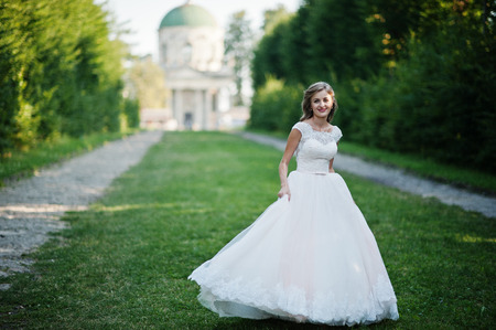 Lonely attractive bride walking on the green alley which leads to a church.